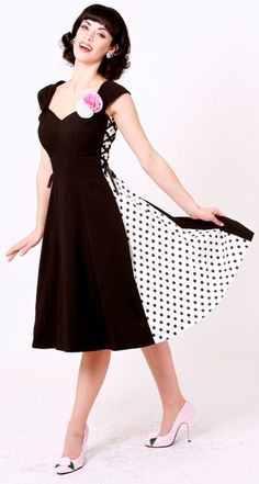 Gathered straps with detachable pink and white satin roses that lead down to a lovely V-neck. Black and white polka dot crepe sides adorned with black decorative ribbon lead to a full circle skirt. This gorgeous pin up dress is brought to you by Bettie Page Clothing.