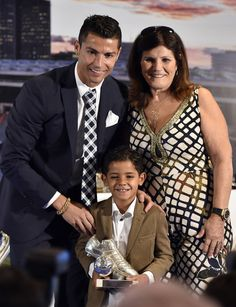 Cristiano Ronaldo Poses with his son Ronaldo and his mother Maria Dolores dos Santos Aveiro during a ceremony for becoming Real Madrid's all-time leading scorer at the Santiago Bernabeu stadium in Madrid on October 2, 2015.