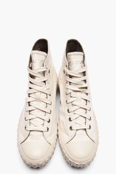 DIESEL //  Sandshell EXPOSURE I High Top Sneakers  32001M050004  High top textile sneakers in off-white. Round rubber cap toe. Tonal lace up closure with gunmetal tone eyelets. Embroidered logo at tongue. Signature scoop pocket, coin pocket and logo rivets at side. Logo flag at coin pocket. Belt loops at heel collar. Square details at tonal foxing. Tone on tone stitching. Cotton upper, rubber sole. Imported.  $185 CAD