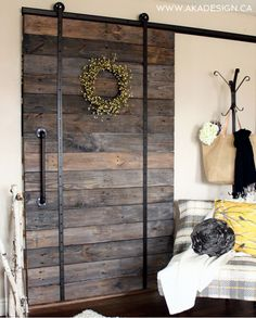 "Add some provincial glamor to a doorway with this sliding barn door, built with character-adding ""dinged and worn"" chunky wooden pallets. Get the tutorial at AKA Design.   - CountryLiving.com"
