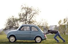 A woman pushes her Fiat 500 in Rome.