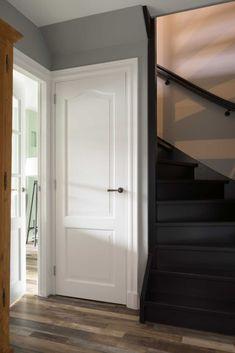 Grijze hal met zwarte trap en witte deuren