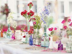 Wild flowers in mismatched bottles #wedding