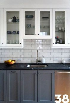 Complete kitchen makeover - contrasting white and grey cabinets, white tile backsplash, black counters