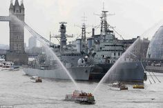 As the procession passed HMS Belfast, a four-gun salute sounded out and the Massey Shaw fi...