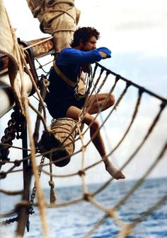 Character on a ship climbs up high among the sails in order to be alone...