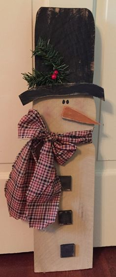 This is a large primitive snowman. He is 24 inches tall, 5 inches wide and 1 inch thick, has a homespun scarf, wooden buttons, pine and berries on his hat. He has a hanger on the back for hanging.