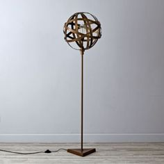 Our Orbital Floor Lamp requires no degree in astronomy.  With an intricately constructed iron shade perched atop a sleek and simple base, this exclusive lamp is ready to grace any room in your home. Nod exclusiveMetal floor base with matte brass finishTriangle bottom and cage shaped shade23W CFL bulb included; also accommodates a 100W max.