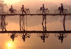 Indonesian villagers push their bicycles across a bamboo bridge as the sun rises behind them in central Java.