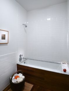 Bathroom Ipe wood floors and tub apron. Marble tub deck over undermount tub. Stack bond white subway tiles