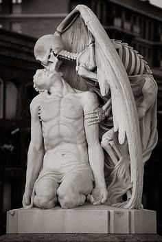 Located in the cemetery of Poblenou Barcelona, this sculpture titled Kiss of Death depicts death (in the form of a winged skeleton) planting a kiss on the forehead of a young man. According to the story, in 1930, the family Llaudet was mourning the death of his son and created this sculpture for his tomb.