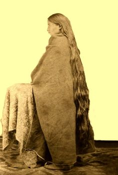 Woman, probably Pueblo, standing next to a cloth covered table, she has very long hair which almost touches the floor. Photo: ca. 1800s.