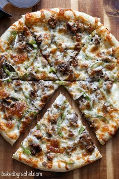 Three cheese thin crust cheesesteak pizza with green peppers and onions. Recipe from /bakedbyrachel/