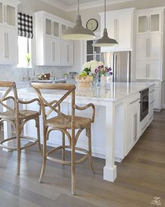 Barstool chairs in nice farmhouse style kitchen with great lighting