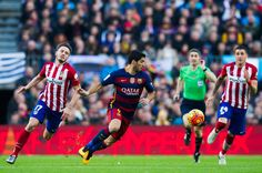 Luis Suarez (C) of FC Barcelona conducts the ball between Saul Niguez (L) and Jose Maria Gimenez (R) of Club Atletico de Madrid during the La Liga match between FC Barcelona and Club Atletico de Madrid at Camp Nou on January 30, 2016 in Barcelona