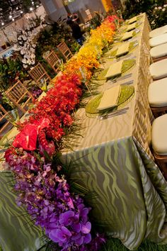 Get Inspired: Vibrant flowers make for a stunning destination wedding reception centerpiece, complementing a simple metallic green tablecloth. Wedding perfect!