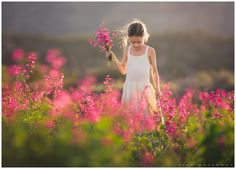 cute little girl picks pink flowers outside in a field for her child portrait shoot near Las Vegas