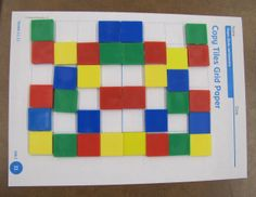 Students play this game of symmetry with a partner.  One person puts a color tile on a 1-inch square; the partner puts the same color on the space in the location that makes the design symmetrical.  (Inspired by the Investigations Math Program 2011)