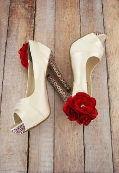 Shoes tell the story of love with these custom wedding shoes by Ellie Wren.  The ivory peep toe pumps feature red and silver rhinestones on the heel and platform, and a trio of red flowers on the ankle.  (www.elliewren.com) #customweddingshoes #ivoryweddingshoes #redweddingshoes #flowerweddingshoes