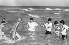 The Beatles take a fully clothed dip in the sea, in Miami, Florida. John warns off an over zealous fan, as hes afraid she might be part-fish. 18th February, 1964.