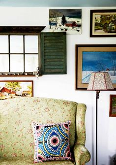 Vintage patterned couch and lamp shade, along with wall art and green window shutters.