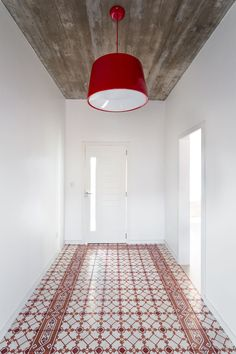 Welcoming you to this modern house is a white entrance hallway, with a bright red pendant lamp and decorative red tiles, and a board-formed concrete ceiling.