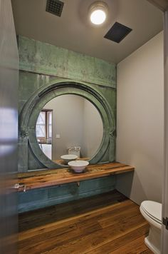 A reclaimed copper window casing salvaged from Albany, New York made its way into this loft in Tribeca, where it now serves as a stunning mirror wall in the powder room. contemporary bathroom by Jane Kim Design Large Round Mirror, Round Mirrors, Circular Mirror, Huge Mirror, Giant Mirror, Round Sink, Wc Decoration, Window Casing, Powder Room Design