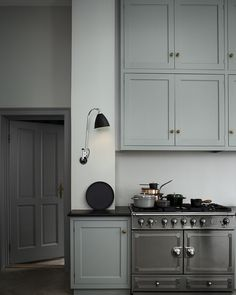 gorgeous stainless steel chrome range cooker, pale grey/green cupboards, wall light