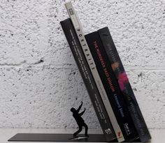 Falling #bookend #supports the #books at a surprising, not straight angle, which makes the whole thing stand out on the shelf and creates interest and humor.  http://thegadgetflow.com/portfolio/falling-books-bookend/