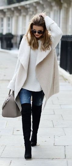 black knee length boots, jeans, a white chunky knit sweater and a white coat