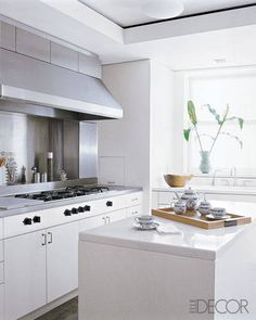The New York kitchen of fashion designer Josie Natori is a minimalist study in white, with cabinetry by St. Charles of New York, a Gaggenau cooktop, and a marble-topped island.