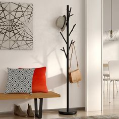 """Featuring a round weighted base and a simplified stem, this freestanding metal coat rack brings a touch of contemporary chic to your foyer with its streamlined design sleek black finish. Adding a dash of whimsy to its design, this coat tree features six """"branches"""" that incorporate eighteen hooks for hanging scarves, hats, and jackets. For an inviting space to greet your guests, roll out an overdyed are rug in the center of the foyer, then arrange a linen-upholstered storage bench against the…"""