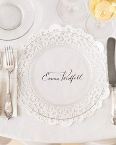 Fabulous idea for placecard seating... print guests' names on lace doilies (or any decoratively cut paper) and use a clear plate on top!