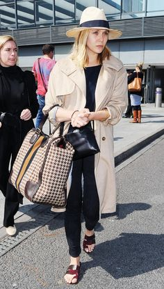Elizabeth Olsen wears all black with a khaki trench coat, Gucci travel bag, slide sandals, and a Fedora