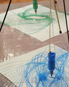 Pendulum Painting - Martha Stewart Kids' Crafts - can skip tripod by attaching a ceiling joist or under kitchen table or something. Anywhere the bottle can swing freely would work.