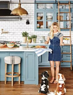 The color of the kitchen cabinets is a mix of baby blue and green. She got the color just right, after several attempts. I love how the glass-front cabinets seem to float on the walls. This look is achieved by leaving the cabinets backless, and exposing the wall of tile.