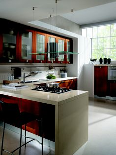 Carol. Tending to the classical but always elegant in its simplicity, here the Aurora Cherry frame door appears on  the base and wall units. The use of frame door units in combination with the very latest materials and colours  transforms the kitchen into a highly contemporary room, perfect for today's needs.