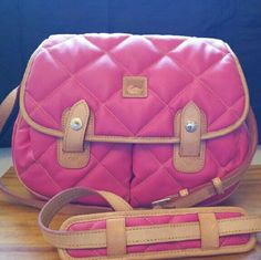 Pink Dooney and Bourke crossbody purse Great condition dooney and bourke. Pink and tan on the outside. Red interior. No discoloration to the exterior. It has an adjustable shoulder strap and snaps to keep the front closed. The interior is clean. Has small discoloration on flap in third picture. You can hardly tell and it's on the inside. I have used it gently. Dooney & Bourke Bags Crossbody Bags