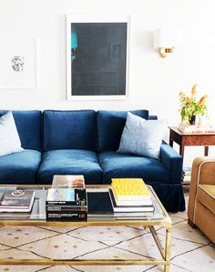 Brass coffee table, blue sofa, with a large neutral area rug.