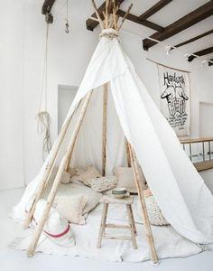 une tente indienne qui complète bien l ambiance artistique, plusieurs coussins, tabouret en bois, couverture blanche pour le sol