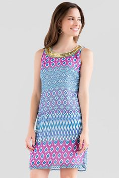 """Skip the necklace when wearing the Avila Printed Dress! This colorful ikat printed shift dress features bold gold beading along the neckline. Sandals & a bracelet finish off the look.<br /> <br /> - 34.5"""" length from shoulder to hem<br /> - 35"""" chest<br /> - 42"""" sweep<br /> - measured from a size small<br /> <br /> - 100% Polyester<br /> - Machine Wash<br /> - Made in U.S.A."""