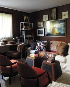 In Howe's  office, the sofa is by Mitchell Gold + Bob Williams, the desk chair is 1970s Italian, and vintage rice boxes serve  as tables; the étagère is from CB2, the large photograph is by Adrien Broom, and the walls are painted in Benjamin Moore's Seed Brown.