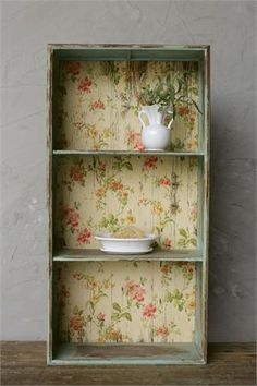This beautiful Vintage Style Shelf with Floral Paper Backing is reminiscent of shelving found in old farmhouse kitchens when vintage wallpaper was used to brighten and add cheer. The metal shelf is three-tiered and features an aged turquoise patina and vintage inspired floral paper on the back.