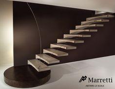 MARRETTI - Escalier à encorbellement, modèle aile en mouette, revêtu de résine type travertin avec rambarde à panneau profilé en plexiglas ou verre.