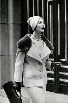 1957 Simone is wearing a grey wool jersey ensemble, the longer jacket has a wide sheared beaver collar by Jacques Heim, handbag is by Durer, Paris