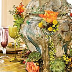 Create a Showpiece | Tuck stems of roses, succulents, pepper berry, and eucalyptus into the holes of an 18th-century glazed ceramic French brazier for a dramatic cascading effect | SouthernLiving.com