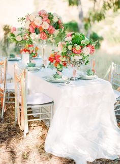 Gorgeous coral and green floral centerpieces for this outdoor reception. #wedding #flowers #tablescape