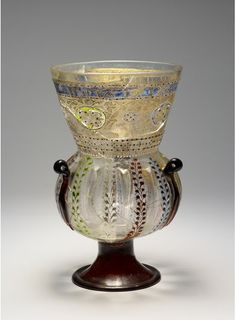 Vase in the shape of a mosque lamp, Probably Venice, c. 1500, Colourless and manganese-violet glass, optically blown in a 12-part ribbed mould, added base and handle eyelets, enamel and gilt-painted decoration, etched gold plating, H. 30.6cm, D. 18.4cm, Photo: Stefan Arendt, LVR, 2011
