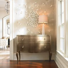 LOVE the wall decor - butterflies gathering at the lamp/light...simple. elegant. metalic painted dresser/table