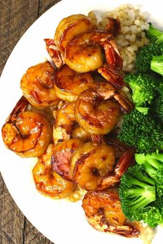 This is a photo of honey garlic shrimp served with broccoli and brown rice on a plate